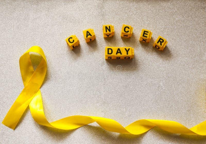 Cinta de oro y palabras compuestas de las hayas plásticas de los niños concepto - un símbolo del cáncer de la niñez, oncología pe imagenes de archivo
