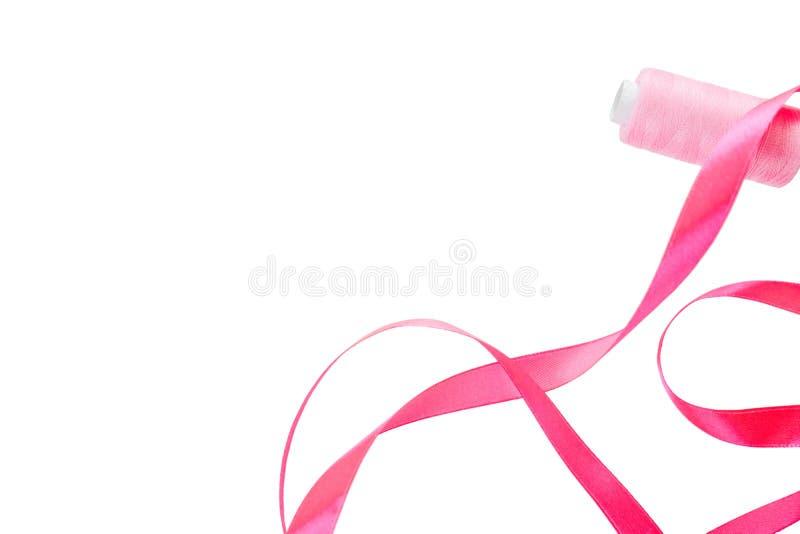 Cinta de satén rizada rosada y un carrete del hilo rosado en un fondo blanco Bandera horizontal, en el lado izquierdo una cinta d imagen de archivo libre de regalías