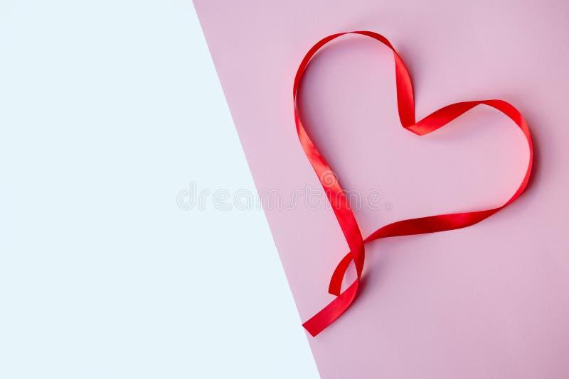 Cinta de seda roja oída, en el fondo del rosa y blanco Madre, mujeres, boda, concepto feliz del st día de San Valentín, 14to FE foto de archivo libre de regalías