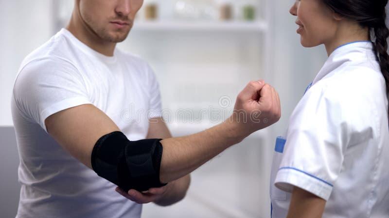 Cinta de verificação paciente da almofada de cotovelo no traumatologist, ferimento dos esportes, cuidados médicos imagens de stock royalty free