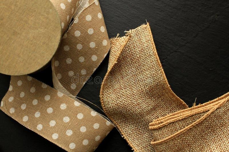 Cinta del algodón y cinta del yute en el rollo de madera en fondo negro fotografía de archivo
