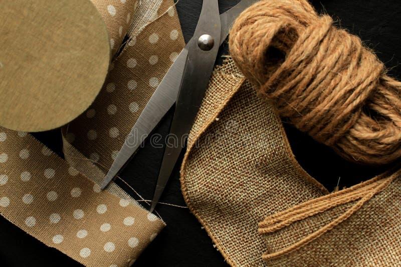 Cinta del algodón, cinta del yute y cordón marrón con las tijeras en fondo negro fotografía de archivo