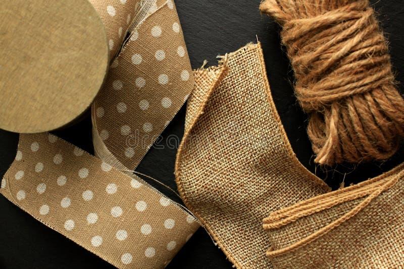 Cinta del algodón, cinta del yute y cordón marrón en fondo negro fotografía de archivo libre de regalías