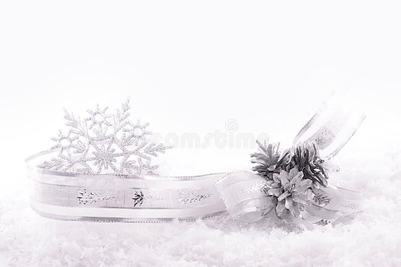 Cinta, estrellas y conos agradable curvados de la plata en nieve fotos de archivo libres de regalías
