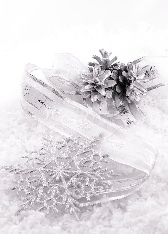 Cinta, estrellas y conos agradable curvados de la plata en nieve imagen de archivo
