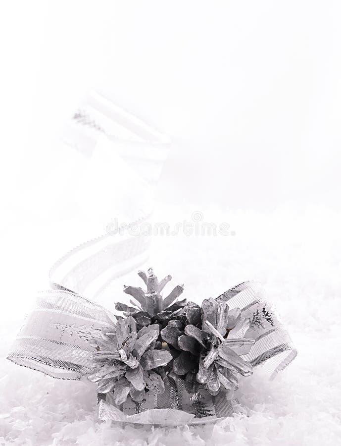 Cinta, estrellas y conos agradable curvados de la plata en nieve imagenes de archivo