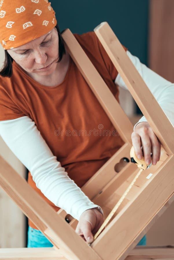Cinta femenina del carpintero que mide el asiento de madera de la silla en taller foto de archivo libre de regalías