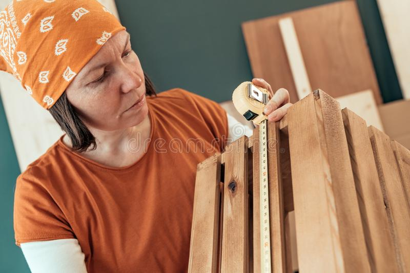 Cinta femenina del carpintero que mide el cajón de madera foto de archivo