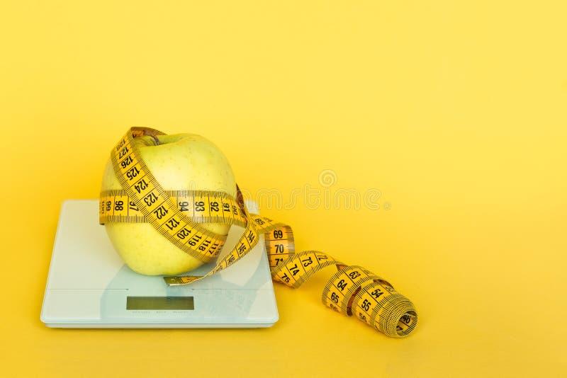 Cinta-línea y manzana amarillas en la escala digital de la cocina en un fondo amarillo Concepto de comer excesivamente, de exceso imagen de archivo