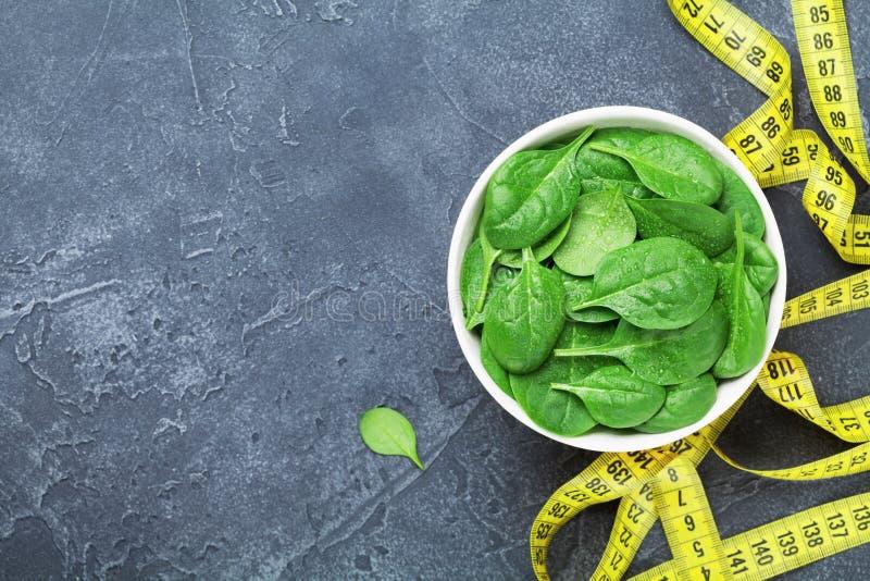 Cinta métrica amarilla y hojas verdes de la espinaca desde arriba Concepto de la comida de la dieta foto de archivo