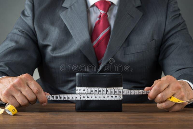 Cinta métrica de Wrapping Wallet With del hombre de negocios imagen de archivo