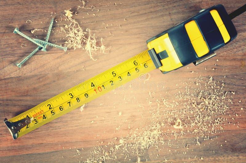 Cinta métrica en la madera imagenes de archivo