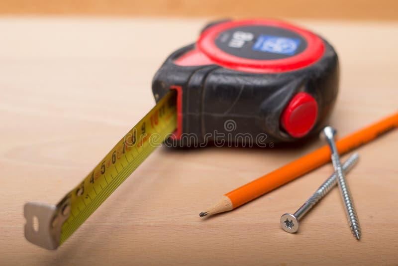 Cinta métrica, lápiz, tornillos en la tabla de madera fotografía de archivo