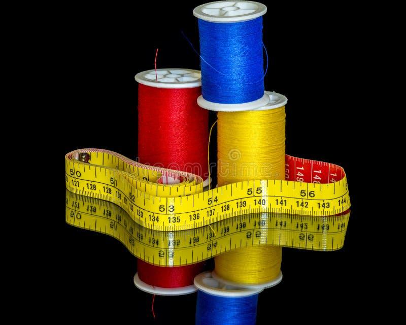 Cinta meauring amarilla e hilo de coser colorido imagen de archivo libre de regalías