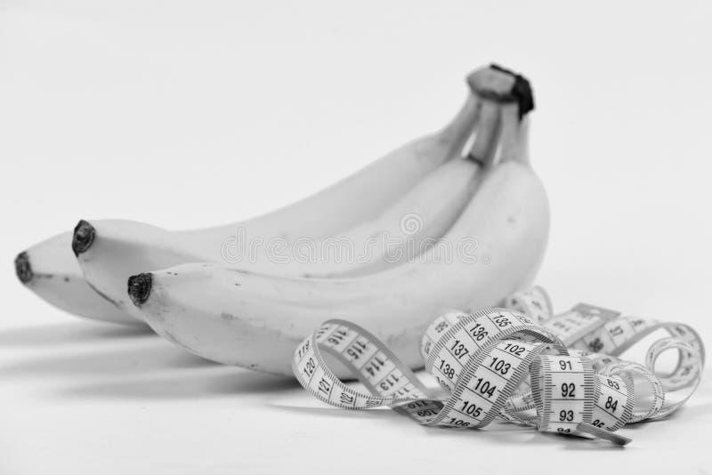 Cinta para medir cerca del manojo de plátanos maduros, aislado en fondo amarillo claro, foco selectivo imágenes de archivo libres de regalías