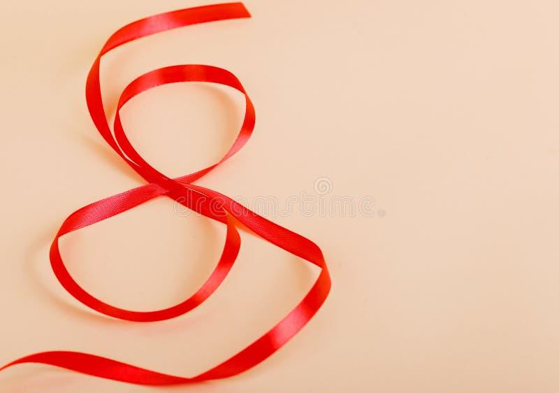 Cinta roja de la celebración del regalo en forma de 8 dígitos en el papel imágenes de archivo libres de regalías