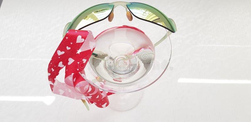 Cinta roja de los corazones y gafas de sol verdes del espejo sobre el vidrio de la vid imagenes de archivo