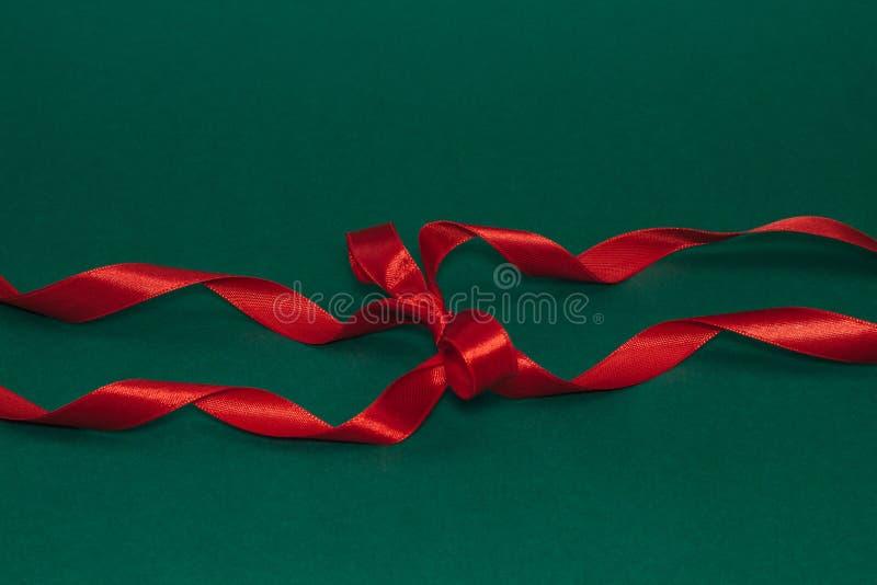 Cinta roja de seda decorativa con un arco en fondo de color verde oscuro imagenes de archivo