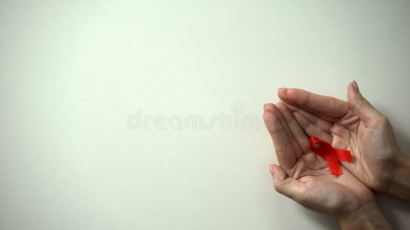 Cinta roja en el d?a femenino de las manos, de las AYUDAS del mundo y del VIH, campa?a de concienciaci?n, primer foto de archivo