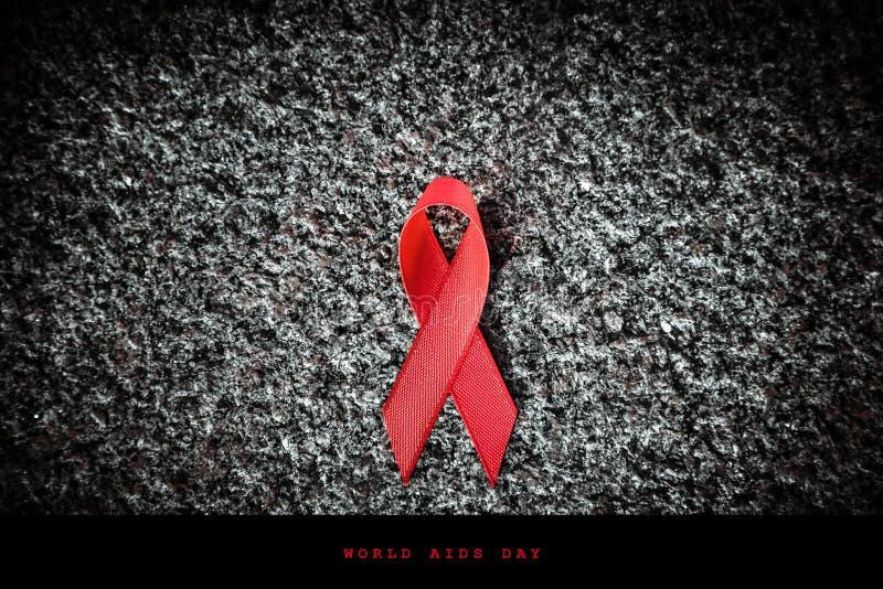 Cinta roja en una piedra, concepto de la cinta roja del Día Mundial del Sida imágenes de archivo libres de regalías