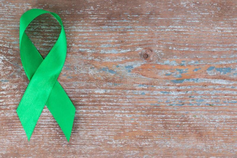 Cinta verde Escoliosis, salud mental y otra, symbo de la conciencia en el fondo de madera con el espacio de la copia fotos de archivo