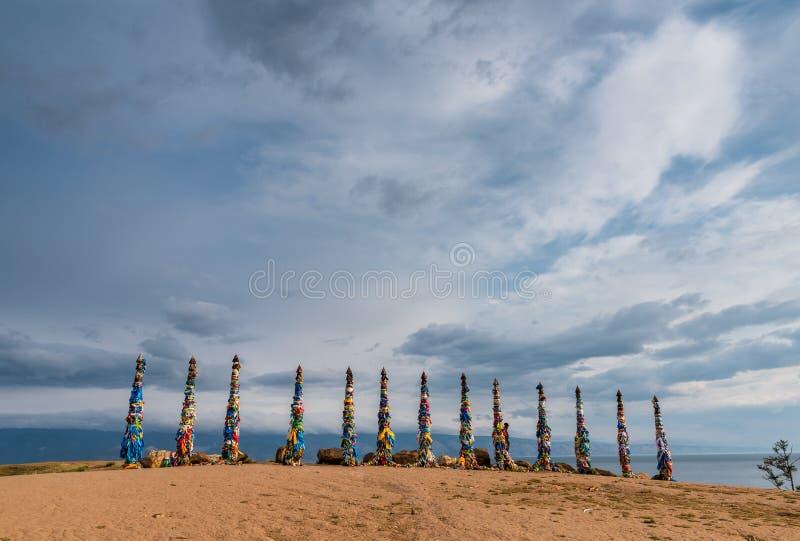 Cintas coloridas en polos de madera en el lago Baikal en Siberia imagen de archivo