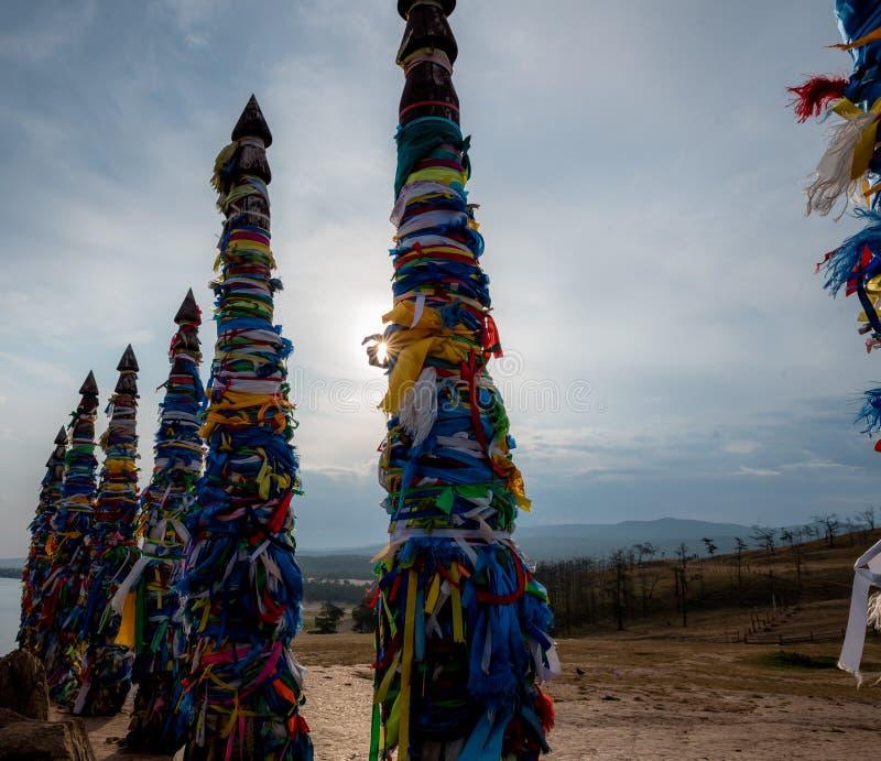 Cintas coloridas en polos de madera en el lago Baikal en Siberia fotografía de archivo libre de regalías