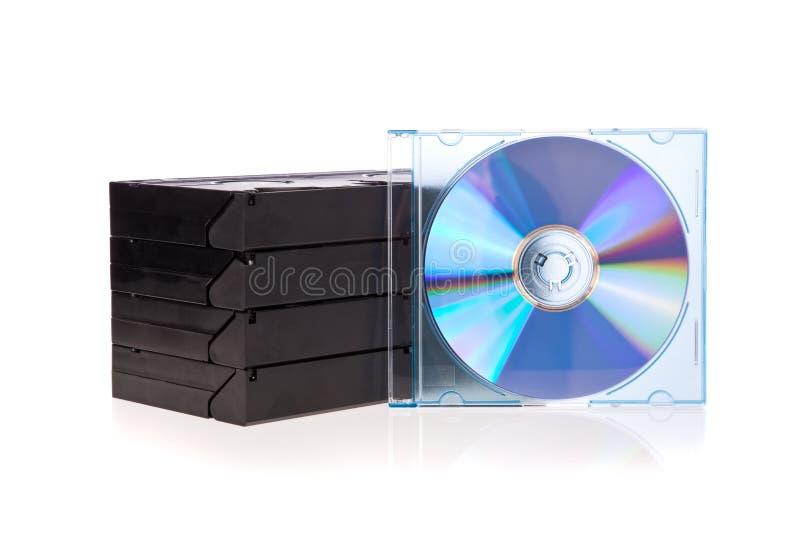 Cintas de cinta de video viejas con un disco de DVD aislado fotografía de archivo