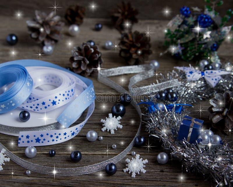 Cintas, gotas, conos para adornar el árbol de navidad Fondo de madera con las nevadas exhaustas entonado fotografía de archivo