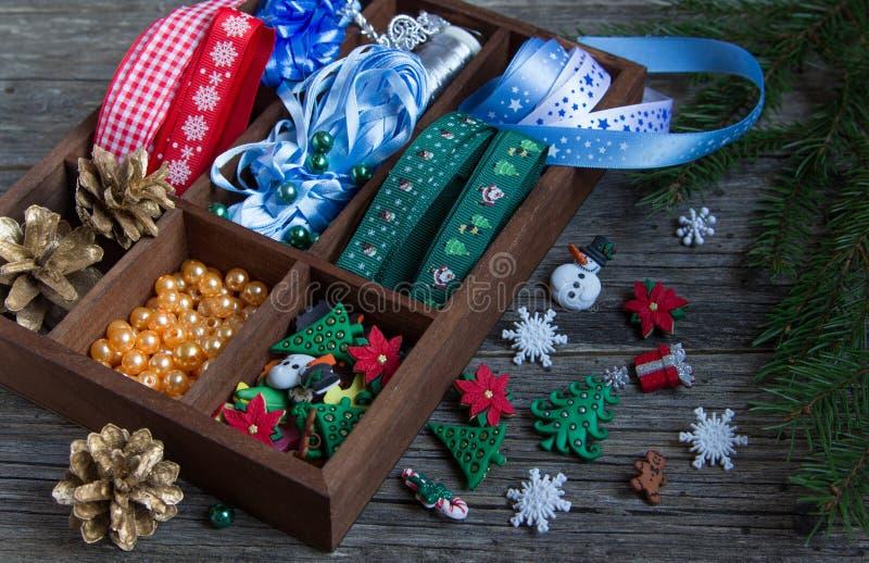 Cintas, gotas, juguetes, artes de la Navidad en una caja de madera imágenes de archivo libres de regalías