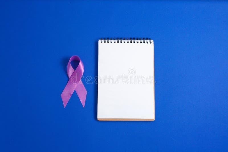 Cintas púrpuras y cuaderno abierto en el fondo azul, enfermedad de Alzheimer, cáncer pancreático, imagen de archivo