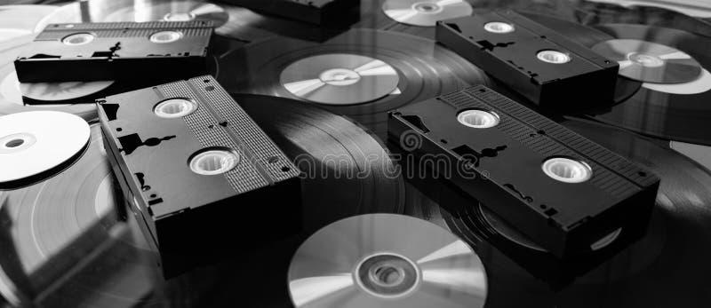 Cintas video de VHS con Cdes, DVDs y los discos de vinilo fotos de archivo libres de regalías