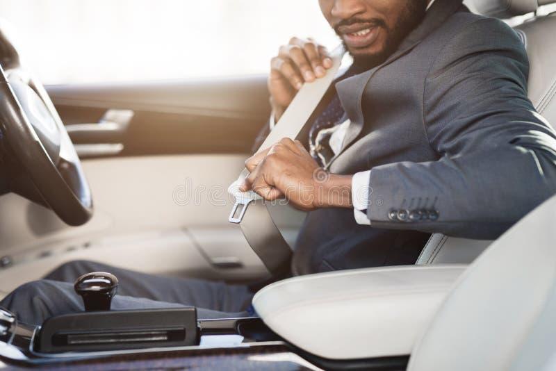 Cinto de segurança afro-americano da asseguração do homem de negócios no carro imagem de stock