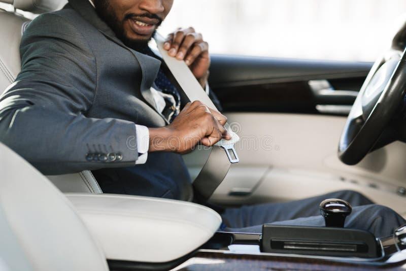 Cinto de segurança da asseguração do homem de negócio no carro fotografia de stock