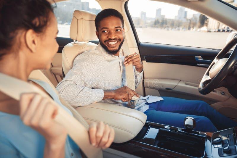 Cintos de segurança vestindo dos pares afro felizes, carro novo de teste fotografia de stock
