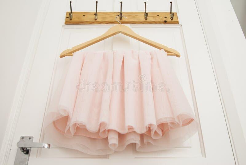Cintre avec la robe rose de tutu de fille d'isolement sur la porte blanche Mode, vêtements de bébé image libre de droits
