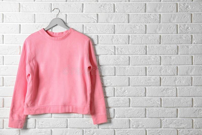 Cintre avec le pull molletonné rose contre le mur Maquette pour la conception photographie stock