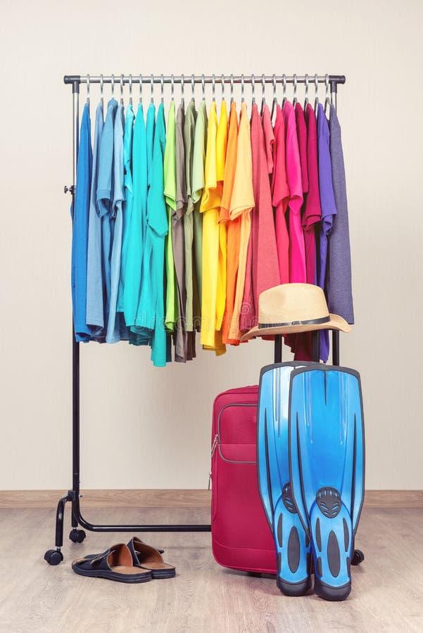 Cintre avec les T-shirts colorés, sandales, valise rouge, chapeau, nageoires pour la natation Honoraires à reposer sur la plage photos stock
