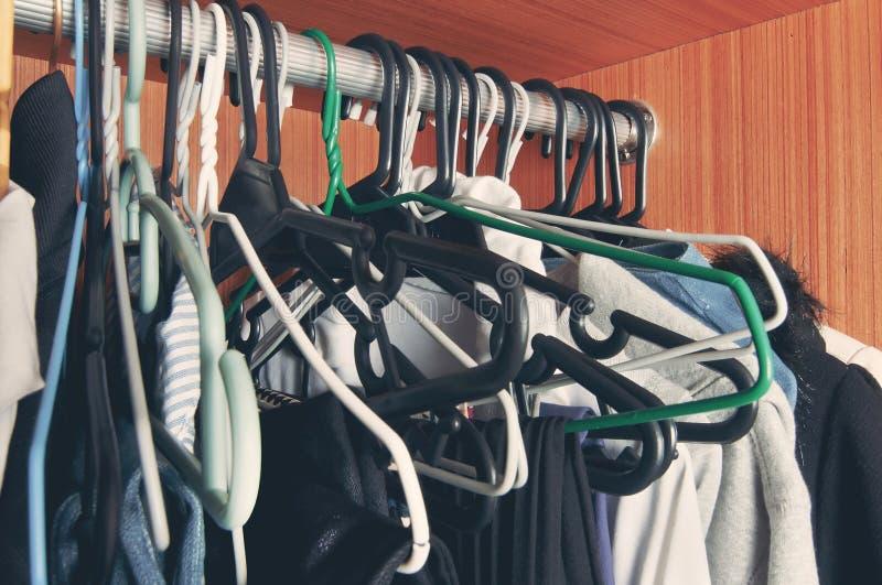 Cintre de manteau malpropre sur le support dans l'armoire photo stock