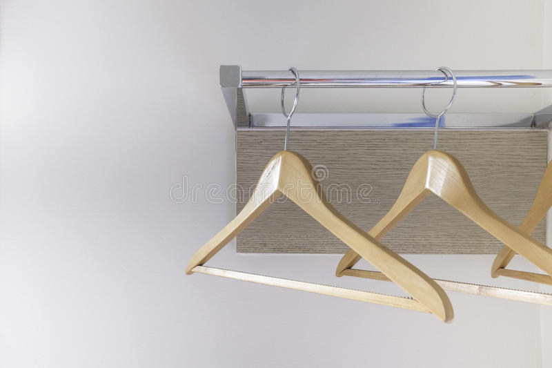 Cintre de tissu en bois sur le rail en métal et le panneau en bois photographie stock libre de droits