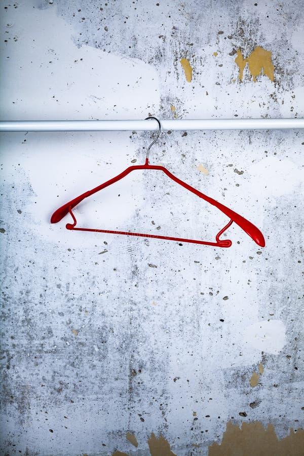 Cintre rouge sur un mur gris photos stock