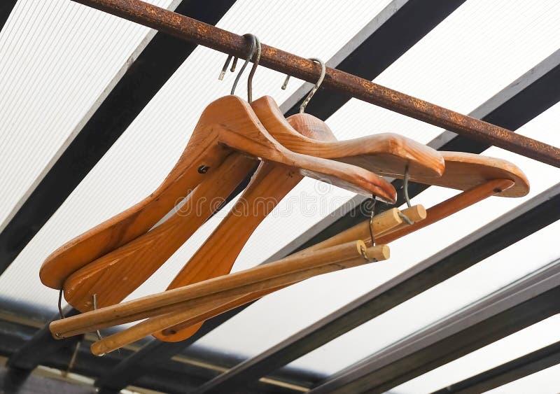 Cintres de manteau en bois sur le support rustique de vêtements photo libre de droits