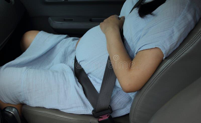 Cinturón de seguridad del desgaste de mujer embarazada en el coche fotografía de archivo
