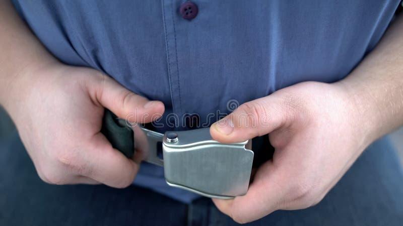 Cinturón de seguridad masculino obeso de la cerradura del pasajero mientras que se sienta en el aeroplano, vuelo seguro imagenes de archivo