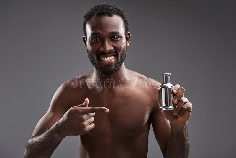 Cintura acima de um homem afro-americano alegre que mostra seu perfume fotos de stock royalty free