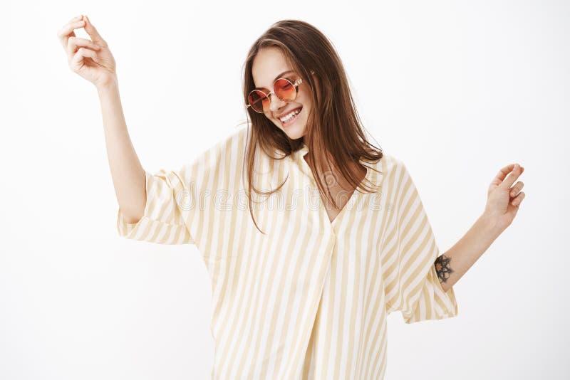 Cintura-acima disparada da fêmea moderna nova deleitada e feliz despreocupada em óculos de sol vermelhos à moda e na blusa listra imagens de stock royalty free