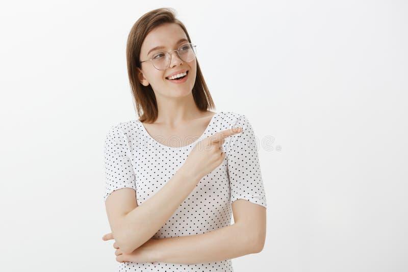 Cintura-acima disparada da mulher bonita satisfeito e alegre nos vidros, sorrindo amplamente, olhando e apontando certo com índic fotografia de stock royalty free