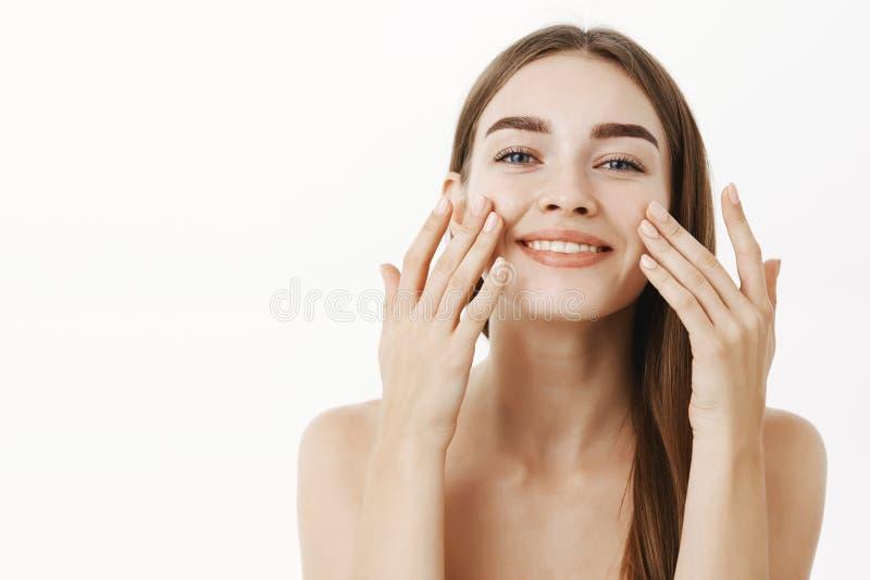 Cintura-acima disparada de encantar a jovem mulher relaxado e delicada que faz o procedimento cosmetological que aplica o creme f foto de stock