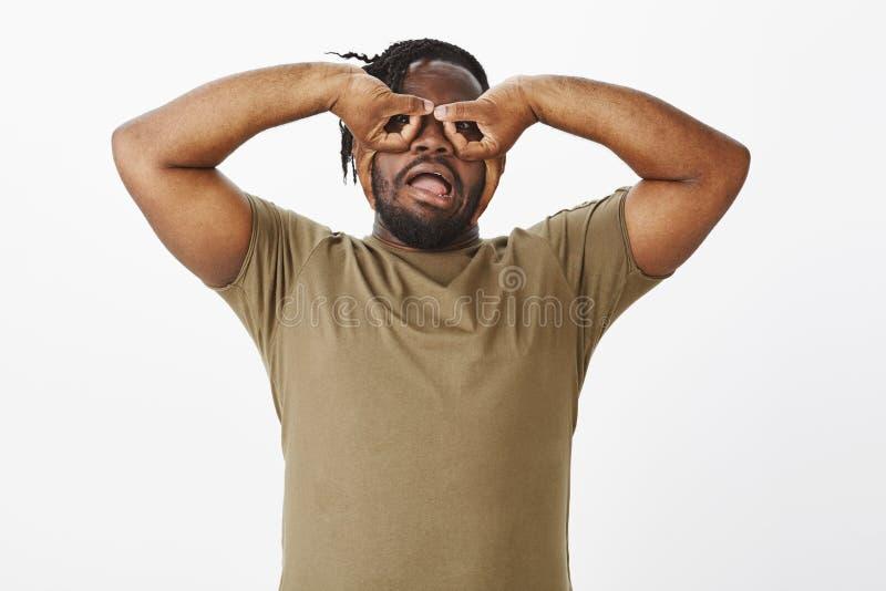 A cintura-acima disparada do indivíduo afro-americano despreocupado engraçado no t-shirt verde-oliva, guardando cede os olhos e a fotos de stock