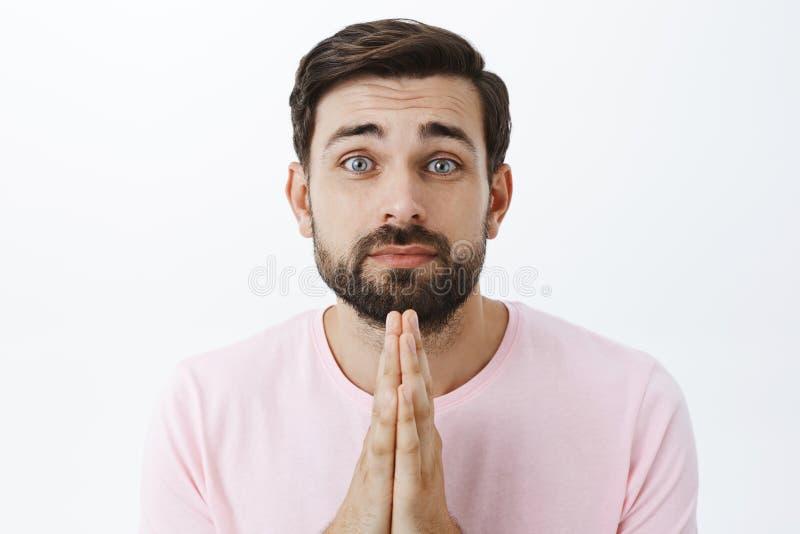 A cintura-acima disparada do indivíduo farpado de cabelo escuro bonito encantador no t-shirt cor-de-rosa que inclina-se guardando fotografia de stock royalty free